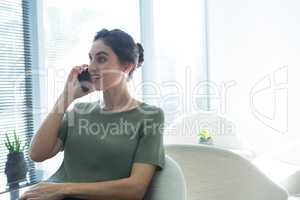 Female executive talking on mobile phone in the office