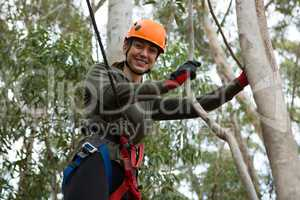 Young smiling woman wearing safety helmet leaning on tree branch in the forest