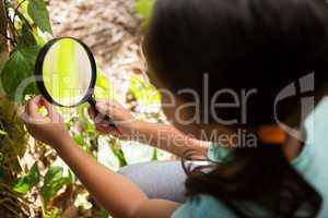 Little girl exploring nature through magnifying glass