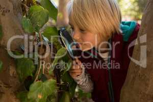 Little girl exploring the nature through a magnifying glass