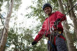 Young hiker man wearing safety helmet holding zip line in the forest during daytime