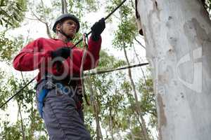 Young man wearing safety helmet crossing zip line in the forest