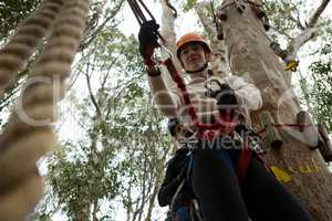 Woman wearing safety helmet fixing carabiner in rope in the forest
