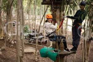 Happy woman leaning on zip line while man standing on wooden platform holding rope