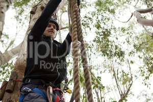Man wearing safety helmet trying to climb the rope in the forest