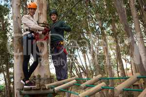 Smiling couple holding zip line cable standing on wooden platform in the forest