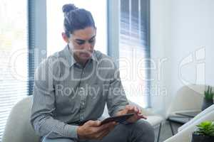 Male executive using digital tablet in waiting area