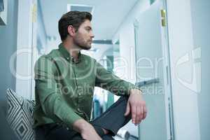 Male executive sitting on chair in waiting area