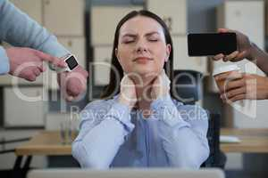 Colleague showing time and mobile phone to frustrated woman
