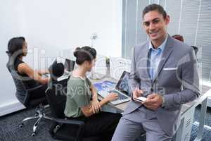 Confident male executive looking at camera while using mobile phone
