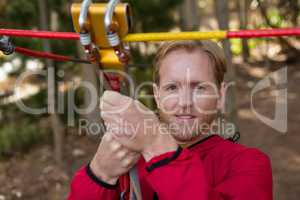 Young hiker man holding zip line pulley in the forest during daytime