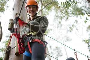 Young woman wearing safety helmet holding zip line cable in the forest
