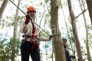 Smiling woman wearing safety helmet holding zip line cable in the forest
