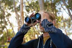 Man hiker exploring nature through binoculars