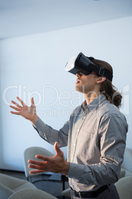Male executive using virtual reality headset in waiting area