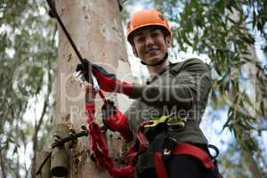 Young hiker woman holding zip line in the forest during daytime
