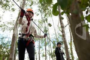 Woman wearing safety helmet holding zip line cable in the forest
