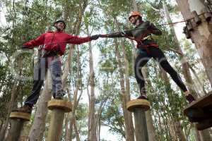 Hiker couple helping each other to cross obstacles in the forest