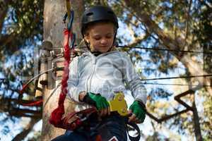 Little girl wearing helmet trying to fix her harness