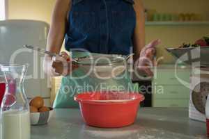 Woman using strainer in kitchen