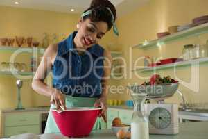 Smiling woman looking into recipe book while whisking mixture in bowl