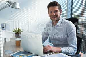 Male executive using laptop while looking at camera