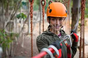 Young smiling woman holding zip line cable in the forest during daytime