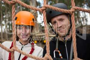 Portrait of smiling couple wearing safety helmet posing through a rope fence in the forest