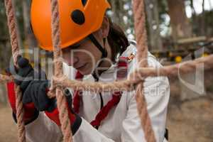 Tired woman wearing safety helmet leaning on rope fence in the forest