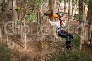 Happy woman wearing safety helmet riding on zip line in the forest