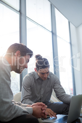Colleagues discussing over laptop in waiting area