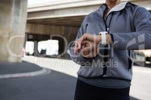Female jogger using smartwatch on a sunny day