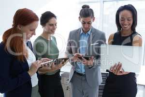 Executives using mobile phone, laptop and digital tablet in the office