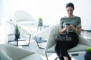 Female executive using mobile phone on chair