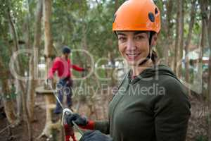 Smiling young woman holding zip line cable and standing in the forest during daytime