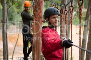 Smiling young man wearing safety helmet crossing zip line cable in background woman waiting for him