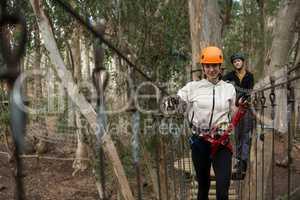 Woman wearing safety helmet crossing zip line bridge in the forest