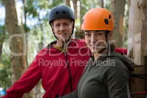 Smiling hiker couple wearing helmet standing in the forest during daytime