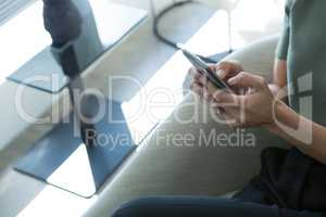Executive sitting on chair using mobile phone in the office