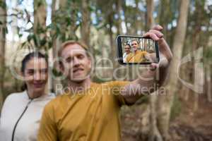 Hiker couple taking selfie with mobile phone in the forest