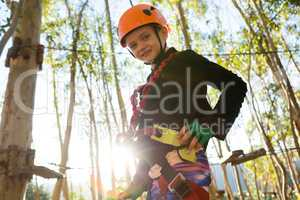 Little girl wearing helmet try to fix pulley