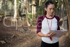 Woman standing in forest holding writing pad