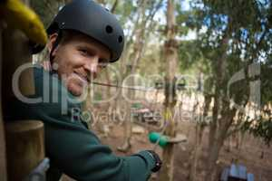 Portrait of smiling man wearing safety helmet looking into camera in the forest