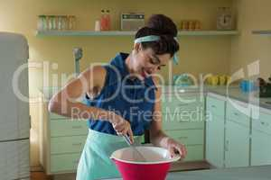 Smiling young woman whisking mixture in bowl