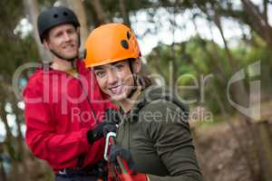 Young hiker couple holding zip line in forest during daytime