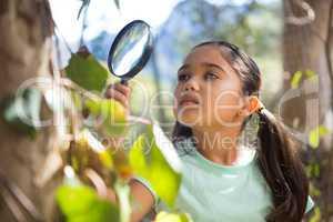 Little girl holding magnifying glass exploring nature