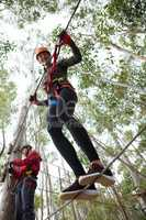 Young smiling woman wearing safety helmet crossing zip line