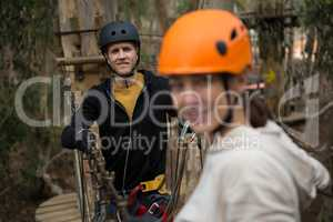 Smiling man wearing safety helmet standing and holding zip line in the forest