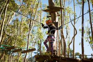 Little girl wearing helmet try to get on wooden bridge