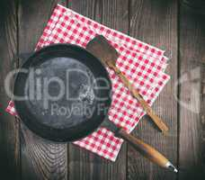 empty black round frying pan with a wooden handle